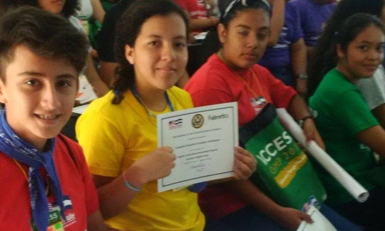 students sitting and holding their diplomas