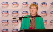 Ambassador Dogu behind the podium during her speech a wall filled with AMCHAM logos behind her