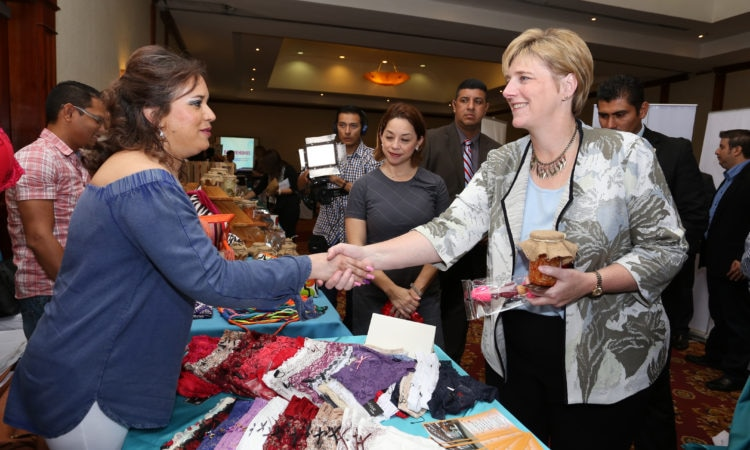 Ambassador Dogu shaking hands with a woman across a table full of clothing