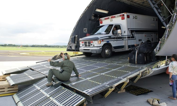 A white ambulance emerges from the cavernous cargo space of the airplane